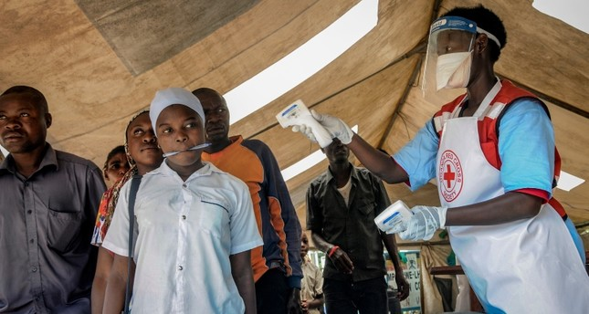 People coming from Congo have their temperature measured to screen for symptoms of Ebola, at the Mpondwe border crossing with Congo, in western Uganda Friday, June 14, 2019. (AP Photo)