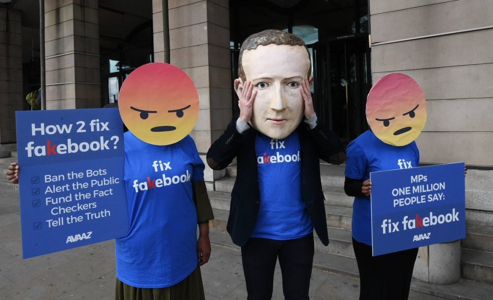 A protester wearing a mask depicting Facebook's CEO, Mark Zuckerberg, protests outside Portcullis House in central London, Apr. 26.