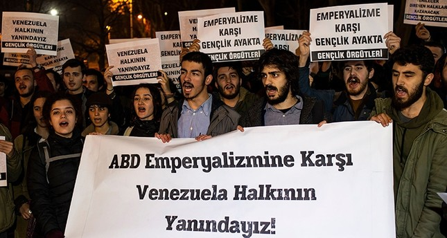 Turkish students hold banners reading We support people of Venezuela! Youth stand against imperialism! as they demonstrate in support of incumbent Venezuelan President Nicolas Maduro in Istanbul on Jan. 28, 2019. AFP Photo