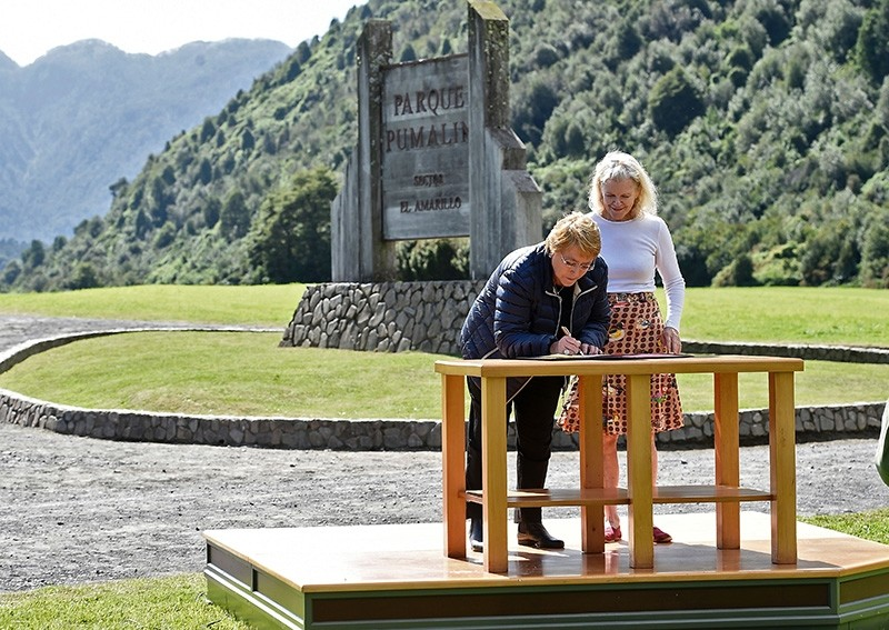 This handout photo released by the Chilean presidency shows President Michelle Bachelet (L) signing a document to receive a donation of 407,000 hectares of land from Kristine McDivitt at Parque Pumalin in southern Chile on March 15, 2017. (AFP Photo)