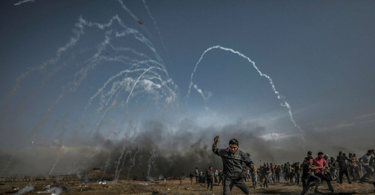 Palestinians protesters run for cover from tear-gas fired by Israeli soldiers during border protests, Gaza Strip, April 27, 2018.