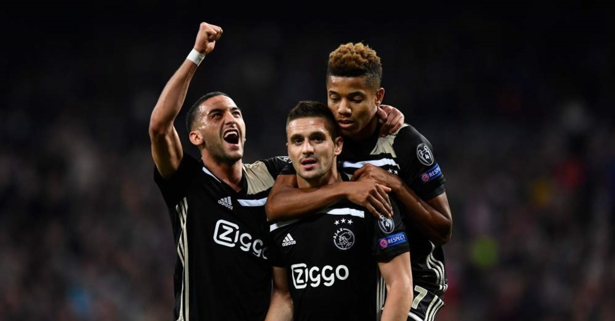 Ajax's Tadic (C) celebrates with Neres (R) and Ziyech after scoring a goal during the UEFA CL match between Real Madrid CF and Ajax in Madrid, March 5, 2019.
