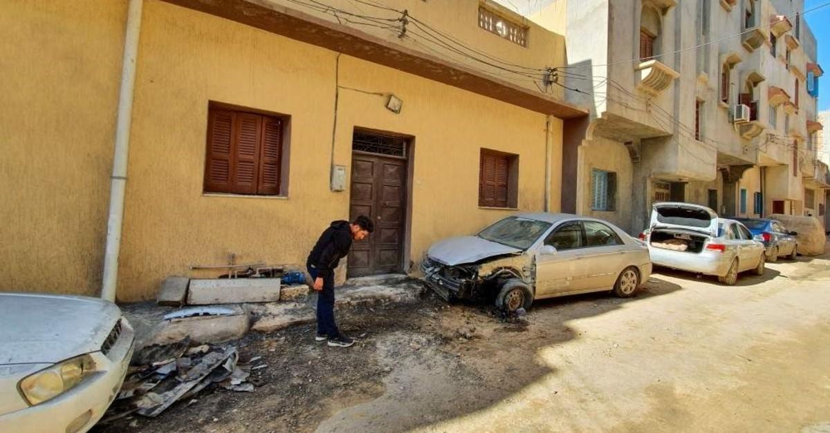 A Libyan man stands next to a damaged car following a rocket blast in Tripoli's southern district of Hadhba al-Badri, Jan. 28, 2020. (Photo by Mahmud TURKIA / AFP)