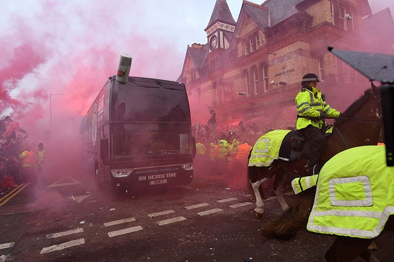 Bottles and cans are thrown at the bus as Manchester City players arrive at the stadium before the UEFA Champions League first leg quarter-final football match between Liverpool and Manchester City, at Anfield stadium on April 4, 2018. (AFP Photo)