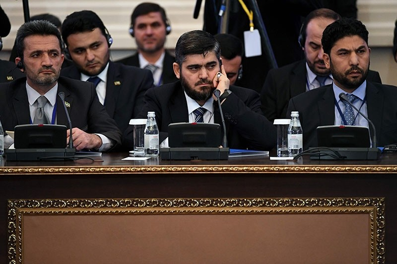 This file photo taken on January 23, 2017 shows chief opposition negotiator Mohammad Alloush (C) of the Jaish al-Islam group attending the first session of Syria peace talks at Astana's Rixos President Hotel. (AFP Photo)