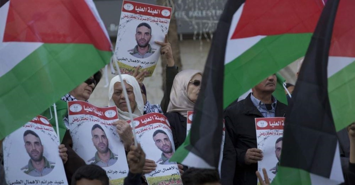 Protesters fly Palestinian flags and carry posters with pictures of a Palestinian prisoner in an Israeli jail, Ramallah, Nov. 26. 2019. (AP Photo)