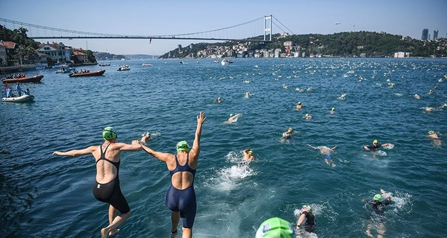 Swimmers jump in the Bosphorous river as they take part in the Bosphorus Cross Continental Swim event on July 23, 2017. (AFP Photo)
