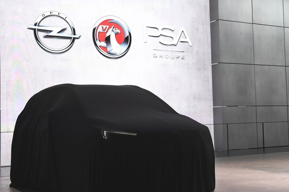 Opel, Vauxhall and PSA signs above a covered car during the first press day of the the Geneva International Motor Show in Geneva.