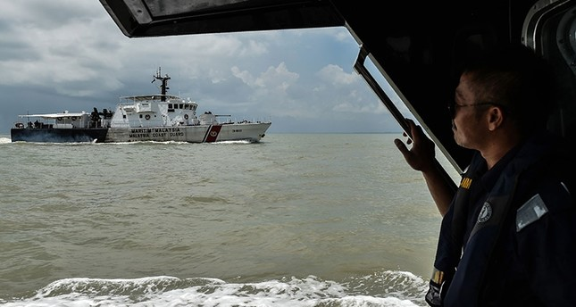 A member of the Malaysian Maritime Enforcement Agency looks out during the rescue operation for the missing sailors from the USS John S. McCain off the Johor coast of Malaysia on August 24, 2017. (AFP Photo)