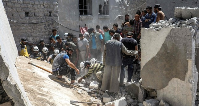 Members of the Syrian Civil Defence White Helmets search for bodies and survivors in a collapsed building following a reported regime airstrike, south of Syria's Idlib province, July 12, 2019.