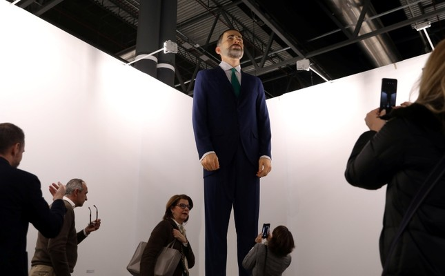 People stand next to the art piece Ninot, 2019, which depicts Spain's King Felipe, by artists Santiago Sierra and Eugenio Merino, during the International Contemporary Art (ARCO) fair in Madrid, Spain, February 28, 2019. REUTERS