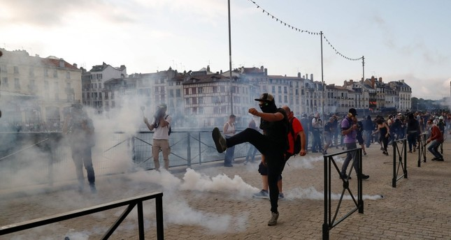 A protester kicks away a 'canister' fired by French security personnel during a demonstration in the city of Bayonne, south-west France on Aug. 24, 2019 AFP Photo