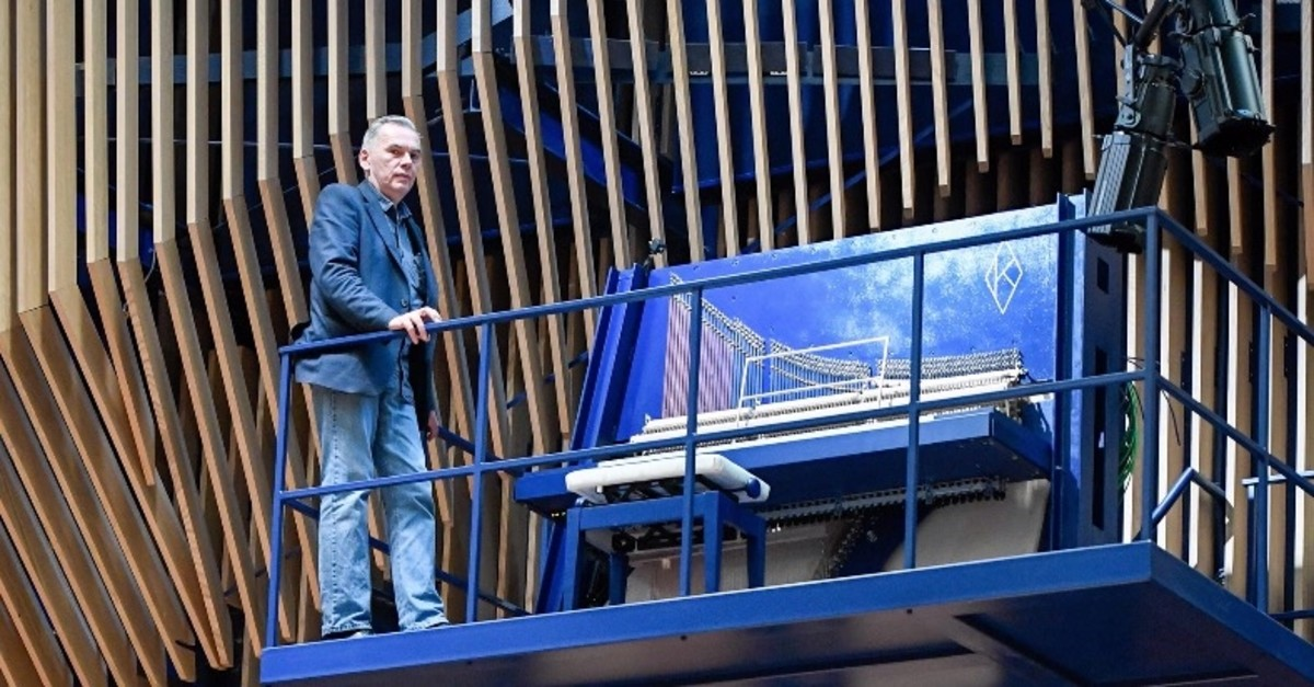 David Klavins stands next to his new creation, the M470i vertical concert grand piano, with a height of 4,70 meters, at the new ,Lativa, concert hall in Ventspils, Latvia, on July 23, 2019.