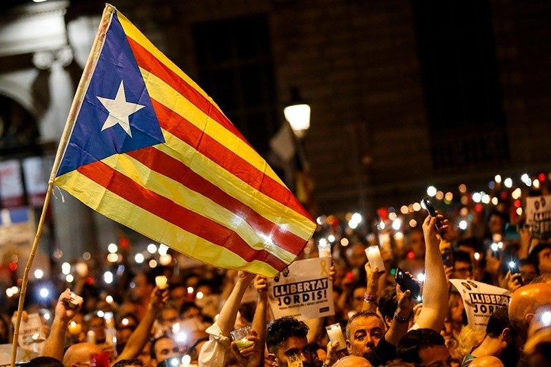 People hold candles and a Catalan pro-independence 'Estelada' flag during a demonstration in Barcelona against the arrest of two Catalan separatist leaders on October 17, 2017. (AFP Photo)