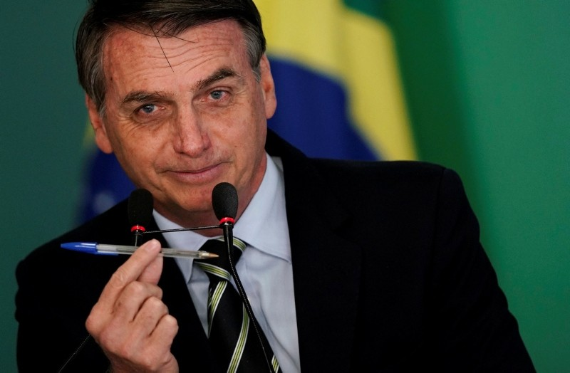 Brazil's President Jair Bolsonaro shows a pen during a signing ceremony of the decree which eases gun restrictions in Brazil, at the Planalto Palace in Brasilia, Brazil January 15, 2019. (Reuters Photo)