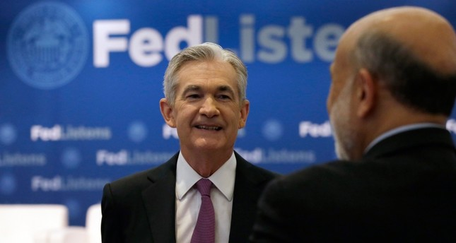 U.S. Federal Reserve Chairman Jerome Powell, left, talks to former Federal Reserve Chairs Ben Bernanke at a conference involving its review of its interest-rate policy strategy and communications, Tuesday, June 4, 2019, in Chicago. (AP Photo)