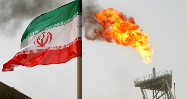 A gas flare on an oil production platform in the Soroush oil fields is seen alongside an Iranian flag in the Persian Gulf, Iran, July 25, 2005. (REUTRES Photo)