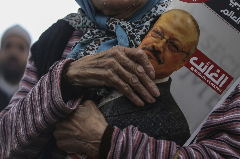 A woman holds a poster during the funeral prayers in absentia for Saudi writer Jamal Khashoggi who was killed last month at the Saudi Consulate in Istanbul, Nov. 1.