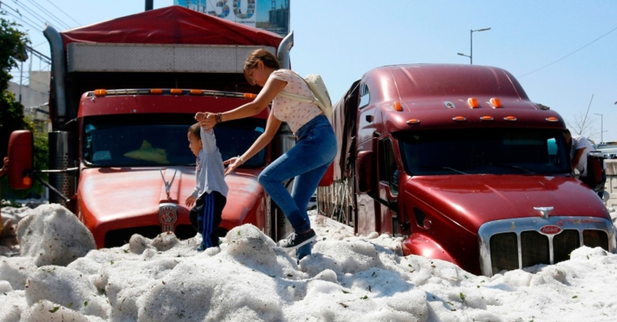 A woman and a child walk on hail in the eastern area of Guadalajara, Jalisco state, Mexico, on June 30, 2019. (AFP Photo)