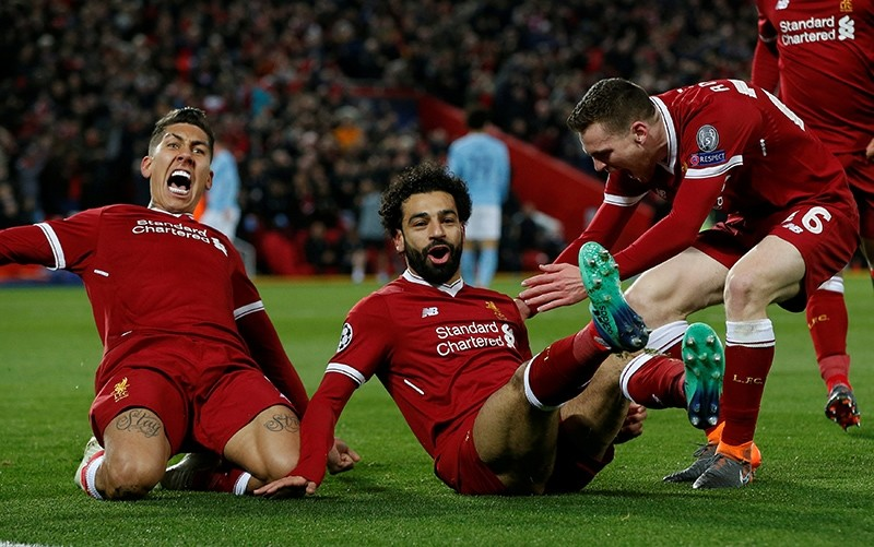 Liverpool's Mohamed Salah, center, celebrates with Roberto Firmino, left, and Andrew Robertson after scoring the first goal in the UEFAu00a0Champions League quarter-final against Manchester City at Anfield, Liverpool, U.K., April 4, 2018. (Reuters Photo)