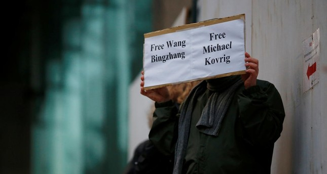 A man holds a sign calling for China to release Wang Bingzhang and former Canadian diplomat Michael Kovrig, who was arrested in China on Tuesday. (REUTERS Photo)