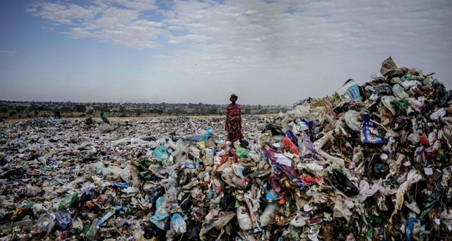 A recycler stands among a tons of plastic rubbish at a sanitary landfill in the industrial city of Bulawayo, Zimbabwe, June 2, 2018. (AFP Photo)