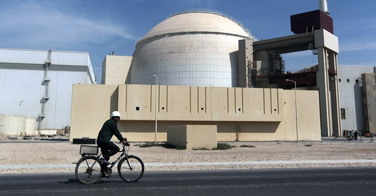 a worker rides a bicycle in front of the reactor building of the Bushehr nuclear power plant in Iran. (AP File Photo)