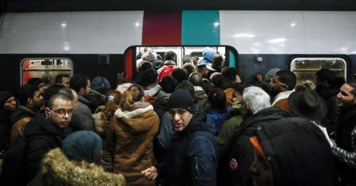Commuters try to enter a packed train (RER) during a general strike action at Gare Du Nord train station, Paris, Dec. 9, 2019. (EPA Photo)