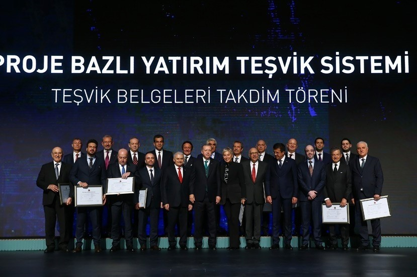 President Erdou011fan (center, front row) granted incentive certificates to the investors at the ceremony for the project-based investment incentives at the Presidential Palace Complex, Ankara, April 9.