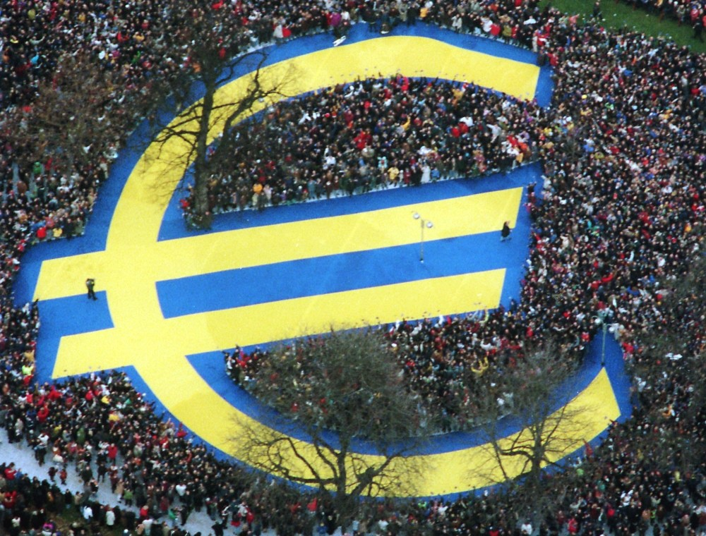 In this Friday, Jan. 1, 1999 photo, thousands of people stand around a huge euro symbol displayed in a park in Frankfurt's banking district on the day of the launch of the euro.