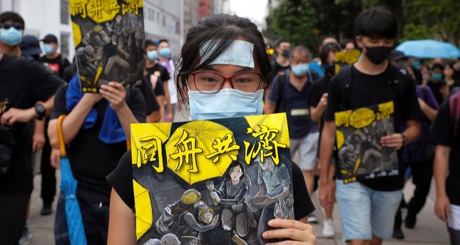 Protesters hold posters depicting protesters, medical worker and people help an injured protester bearing the words Together as they take part in the anti-extradition bill protest march at Shum Shui in Hong Kong, Sunday, Aug. 11, 2019. (AP Photo)