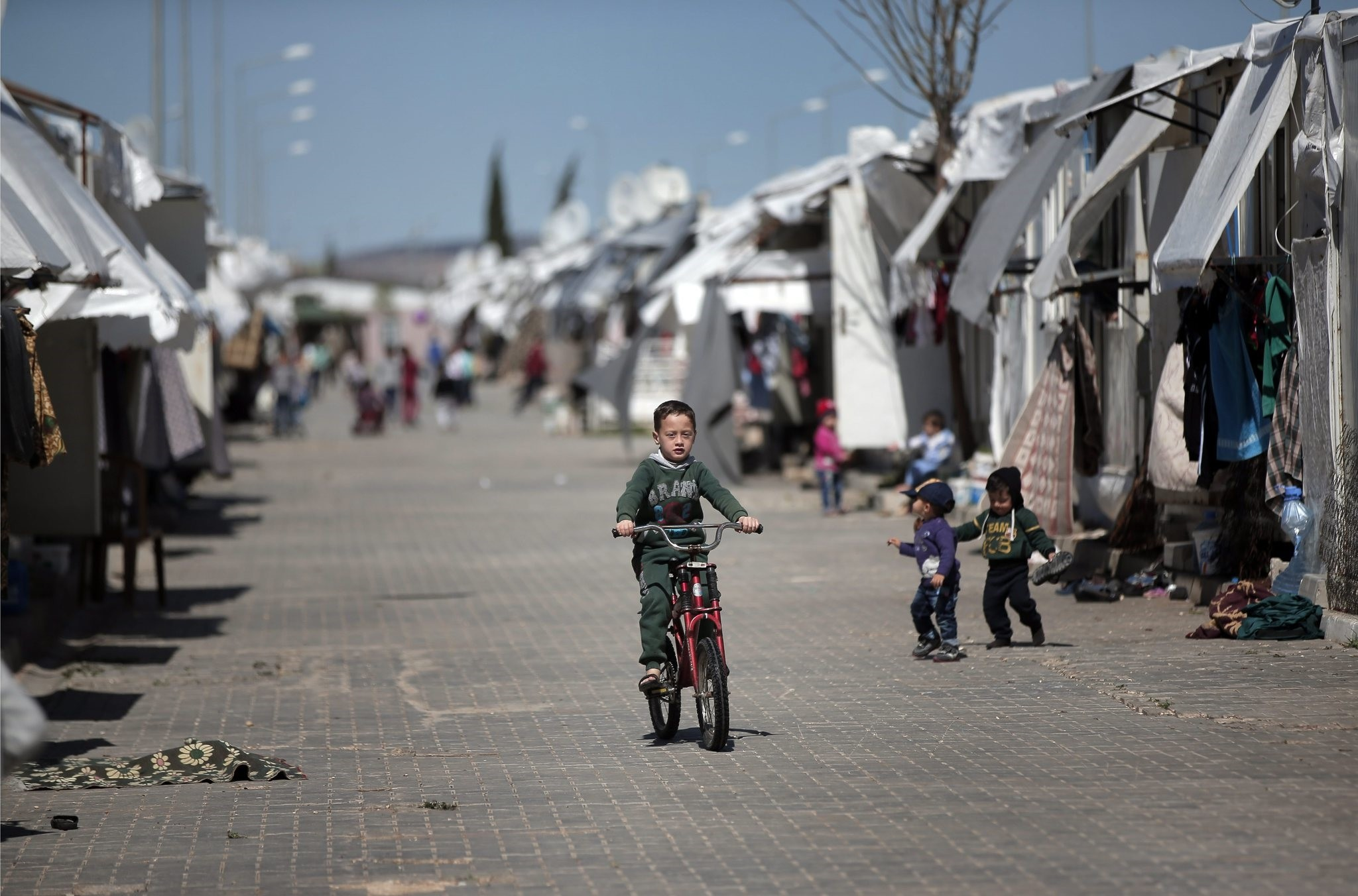 Syrian refugee child rides his bike at the u00d6ncupu0131nar refugee camp, in the border province of Hatay, March 17, 2016.