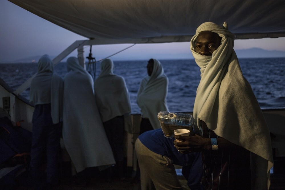 Migrants stand on the deck of a rescue boat off the coast of Libya, Aug. 2.