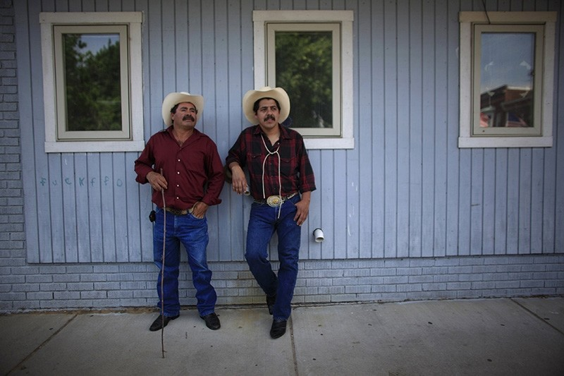 In this May 6, 2012, file photo, two cowboys watch a Cinco de Mayo celebration in Beardstown, Illinois, where approximately 900 immigrant workers from 34 countries are employed at the Cargill meat packing plant. (Reuters Photo)