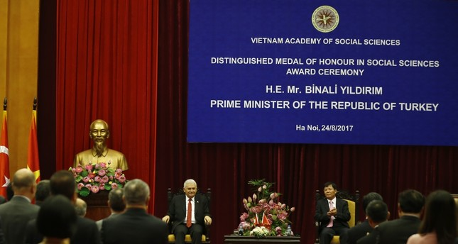 PM Yıldırım (L) attends an awards ceremony at the Vietnam Academy of Social Sciences where he was granted a distinguished medal of honor.