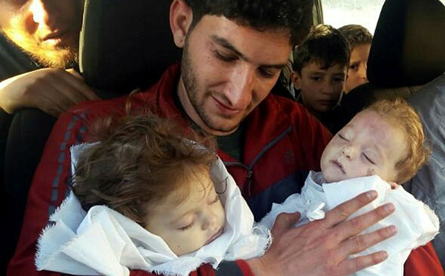 In this picture taken on Tuesday April 4, 2017, Abdul-Hamid Alyousef, 29, holds his twin babies who were killed during an Assad regime chemical weapons attack, in Khan Sheikhoun in the northern province of Idlib, Syria. (AP Photo)