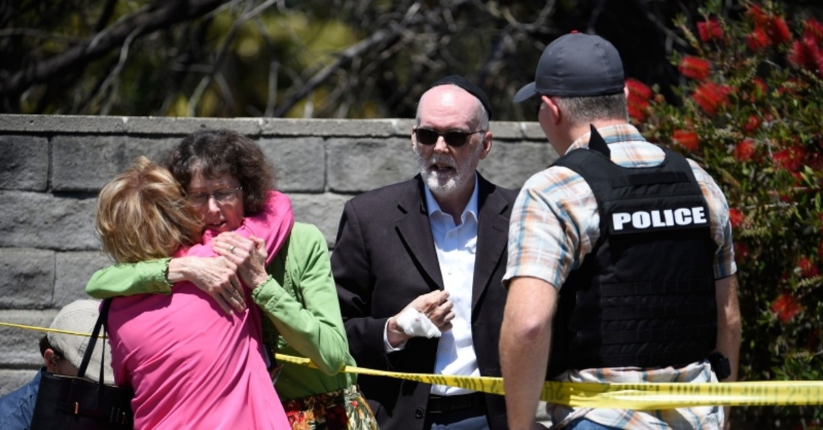 Two people hug as another talks to a San Diego County Sheriff's deputy outside of the Chabad of Poway Synagogue Saturday, April 27, 2019, in Poway, Calif. (AP Photo)