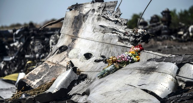 File photo taken on July 26, 2014 shows flowers laid on a piece of the Malaysia Airlines plane MH17, near the village of Hrabove (Grabove), in the Donetsk region. (AFP Photo)