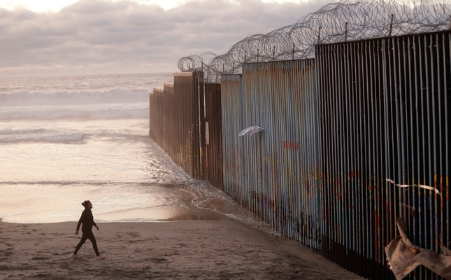 In this Jan. 9, 2019 file photo, a woman walks on the beach next to the border wall topped with razor wire in Tijuana, Mexico. (AP Photo)