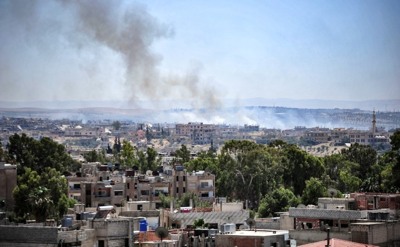 A handout picture released by the official Syrian Arab News Agency (SANA) on June 27, 2018 shows smoke rising above opposition held areas from government forces' bombardment in the southeastern part of the city of Daraa in southern Syria. (AFP Photo)