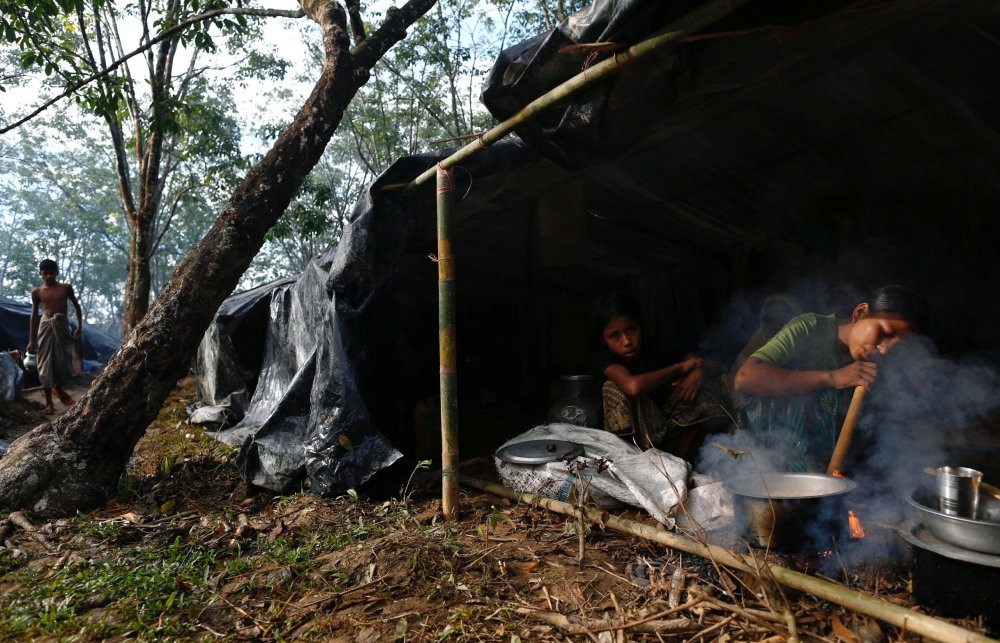 A Rohingya refugee cooks food in her temporary shelter at the Kutupalong makeshift refugee camp in Cox's Bazar, Bangladesh, Sept.14.