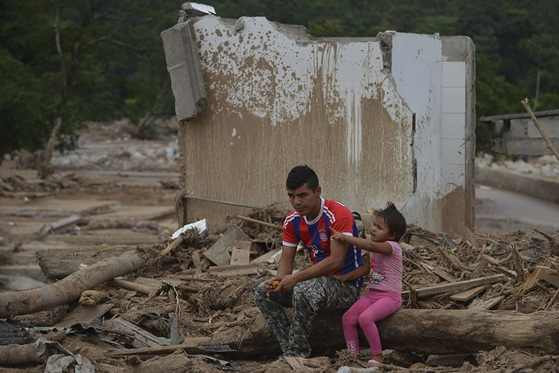A man and his daughter are in the middle of the rubble by a mudslide caused by heavy rains in Mocoa, Putumayo department, Colombia on April 4, 2017. (AFP Photo)
