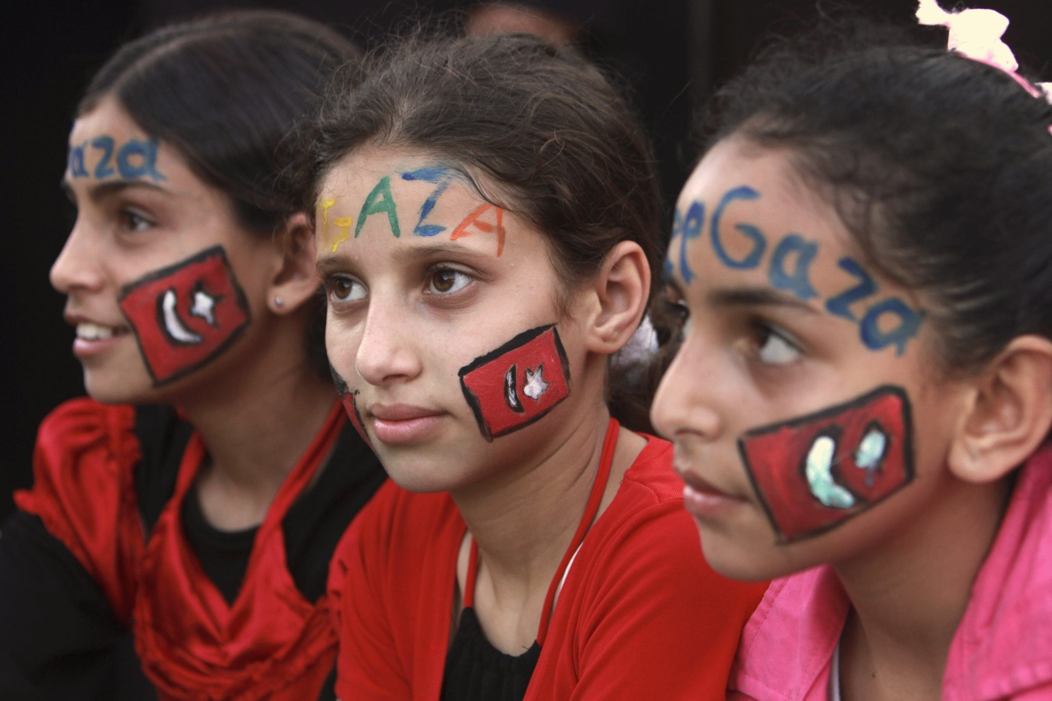 Palestinian children, with the Turkish flags painted their face, attending a protest against the Israeli naval commando raid on a flotilla attempting to break the blockade on Gaza, in Gaza City, June 2, 2010.
