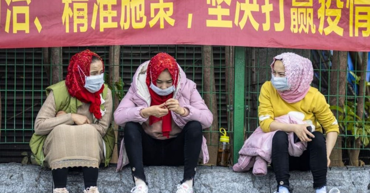 Uighur women wait at the main railway station wearing protective masks for protection of COVID-19, Guangzhou, China, Feb. 12, 2020. (EPA Photo)