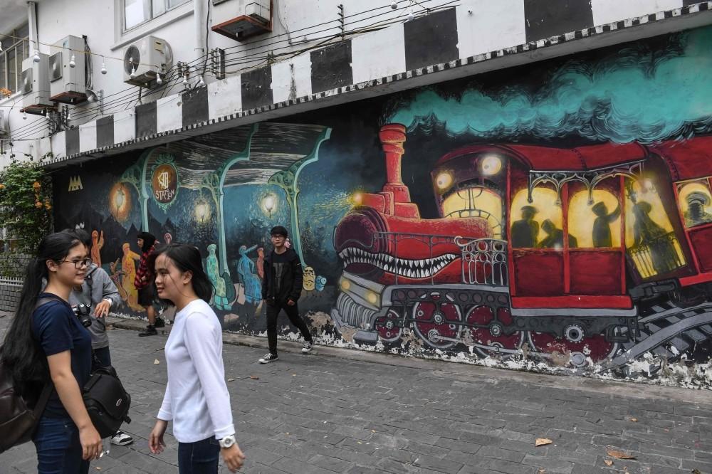 Visitors walking next to graffiti at ,3A Station,, a graffiti hub and street art area in Ho Chi Minh City. (AFP Photo)