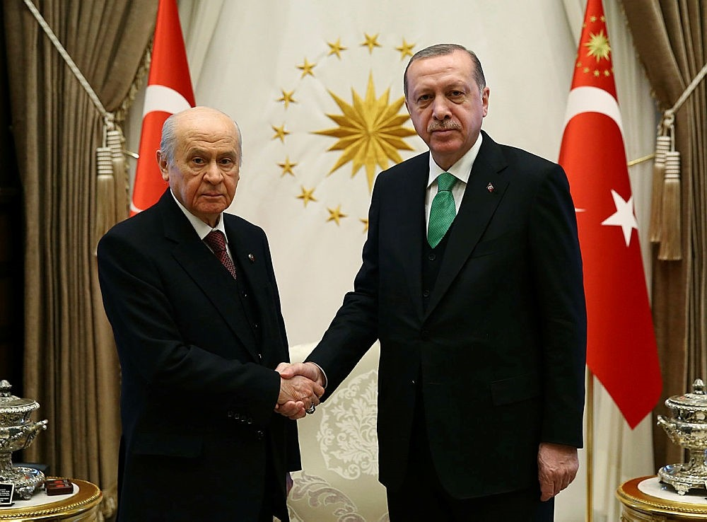 Turkey's President and leader of ruling Justice and Development Party Recep Tayyip Erdogan, right, shakes hands with Devlet Bahceli, leader of opposition Nationalist Movement Party, before their talks in Ankara, Turkey, Sunday, Feb. 18, 2018.  (Pool