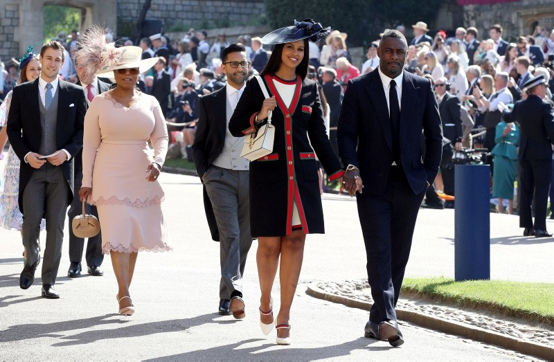 Idris Elba and Sabrina Dhowre followed by Oprah Winfrey (fourth right) arrive at St George's Chapel at Windsor Castle for the wedding of Meghan Markle and Prince Harry. (AP Photo)