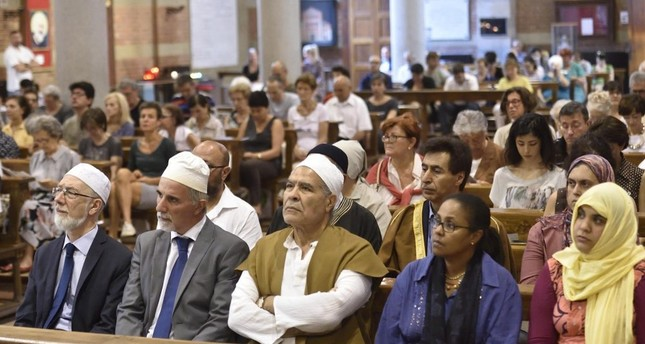 Members of the congregation in Santa Maria Caravaggio Church in Milan during a multi faith service organized by Italy's Islamic Religious Community (COREIS), July 31.