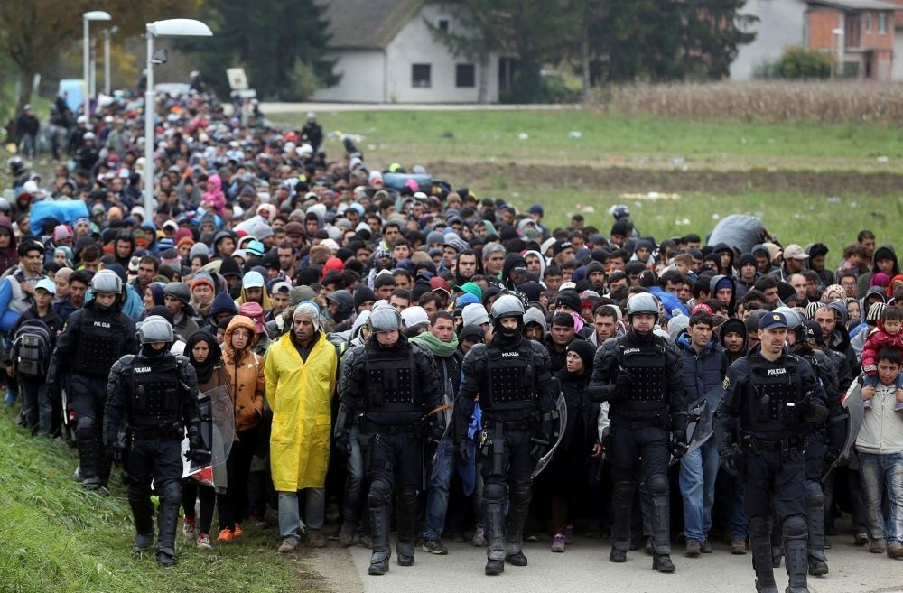 Slovenian police officers escort about 1,000 migrants from border crossing with Croatia.