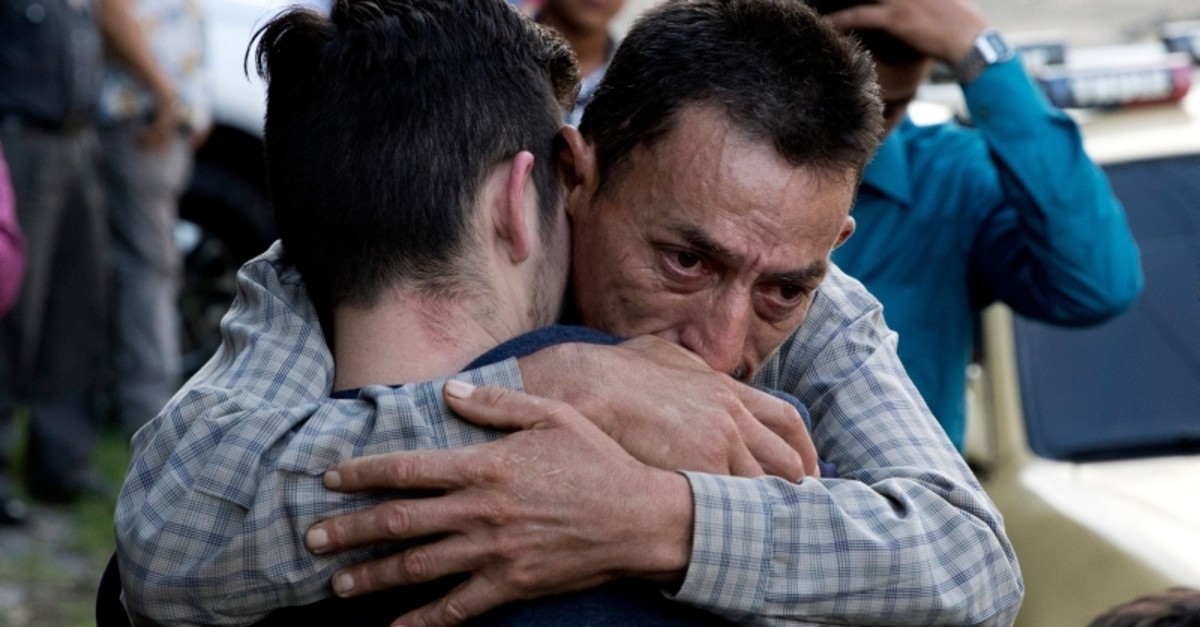 In this Oct. 9, 2019 photo, a father hugs his son outside the Migrant Assistance Office in San Salvador, El Salvador. Buses with deported Salvadorans, such as the son, arrive every day from the U.S. and Mexico. (AP Photo)